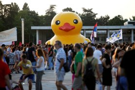 Protesters with flags walk past a rubber duck during protest against Belgrade Waterfront project