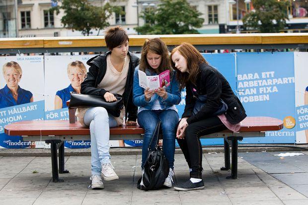 Three young swedish girls read an electi