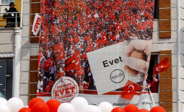 People wave national flags as they wait for arrival of Turkish President Tayyip Erdogan during a ceremony in Istanbul
