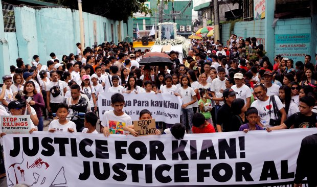 Mourners display a streamer during a funeral march for Kian delos Santos, a 17-year-old student who was shot during anti-drug operations in Caloocan